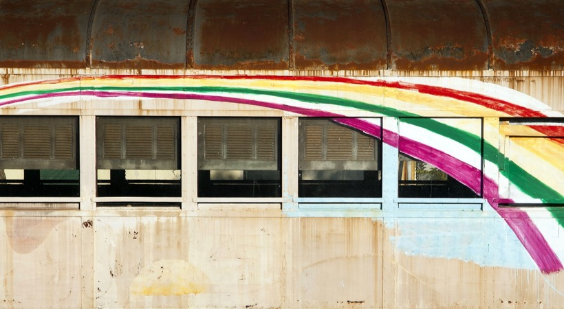 14187804 - old train carriage in the desert with a rainbow painted on it